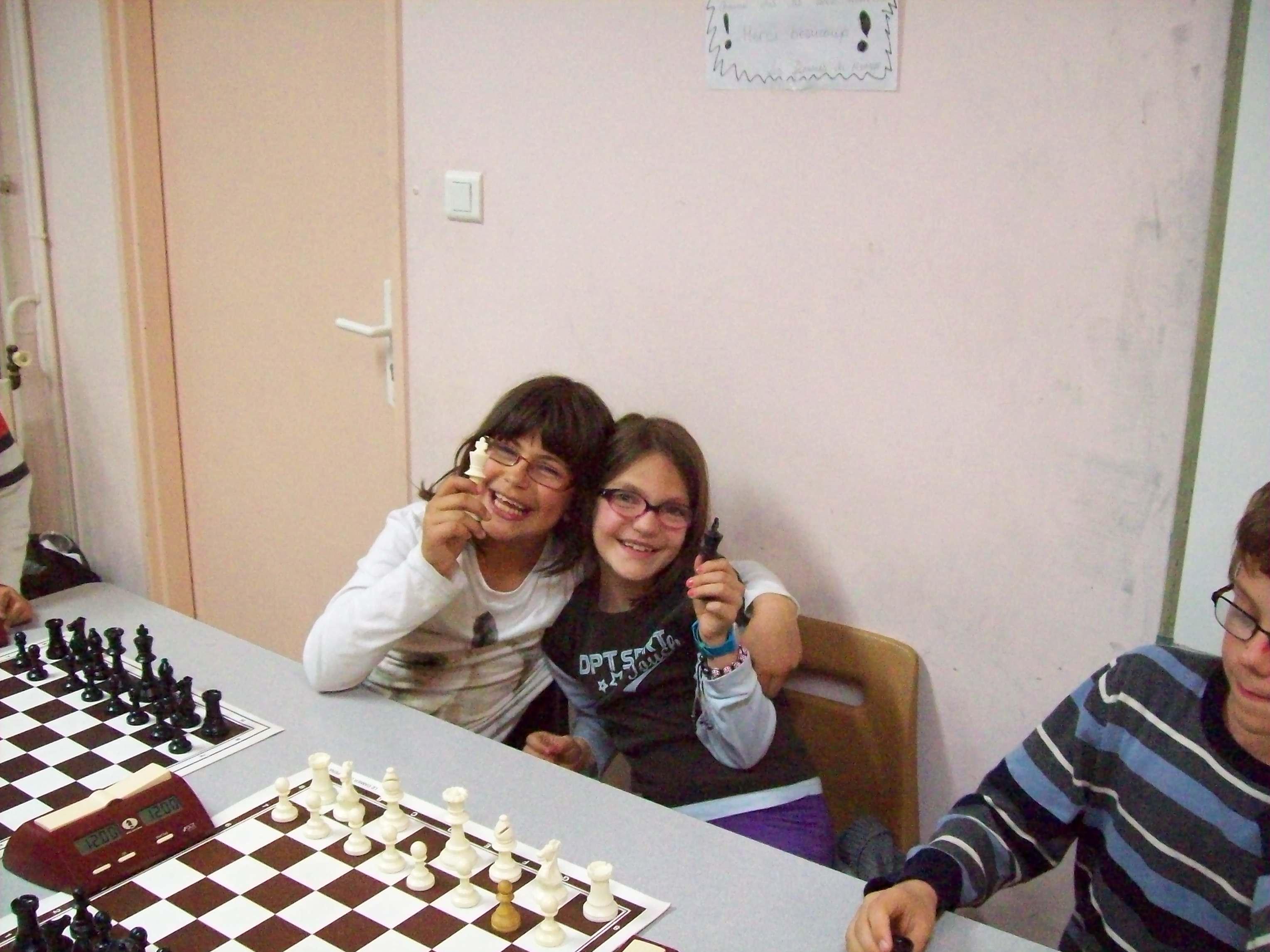 Deux enfants montrent des pièces de jeu d'échecs